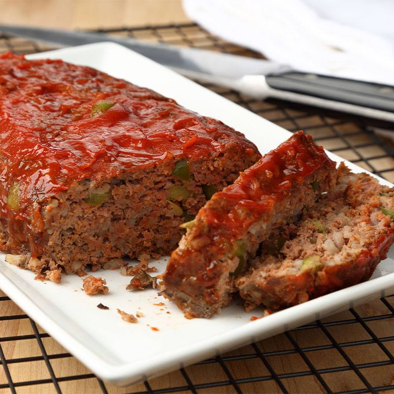 Two slices of Homestyle Meatloaf sit next to the remaining intact meatloaf on a white serving platter.