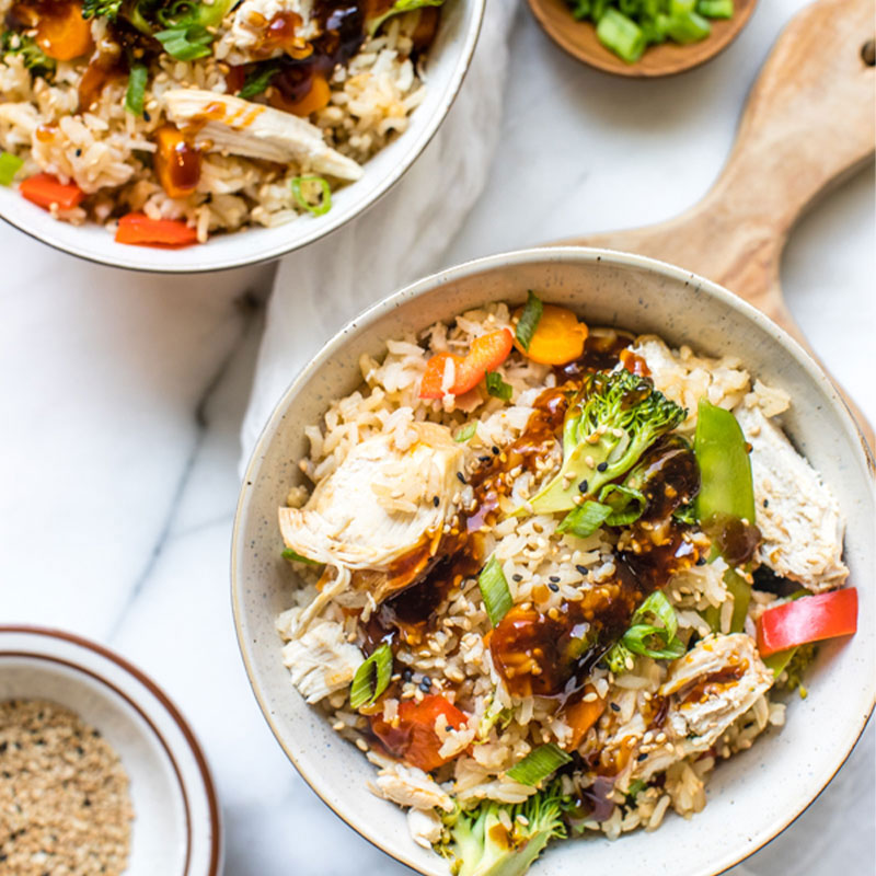 Overhead shot of a Teriyaki Chicken Rice Bowl with broccoli and green onion.