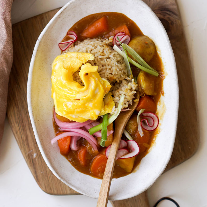 Overhead shot of Japanese Brown Rice Curry in a white dish topped with an egg.