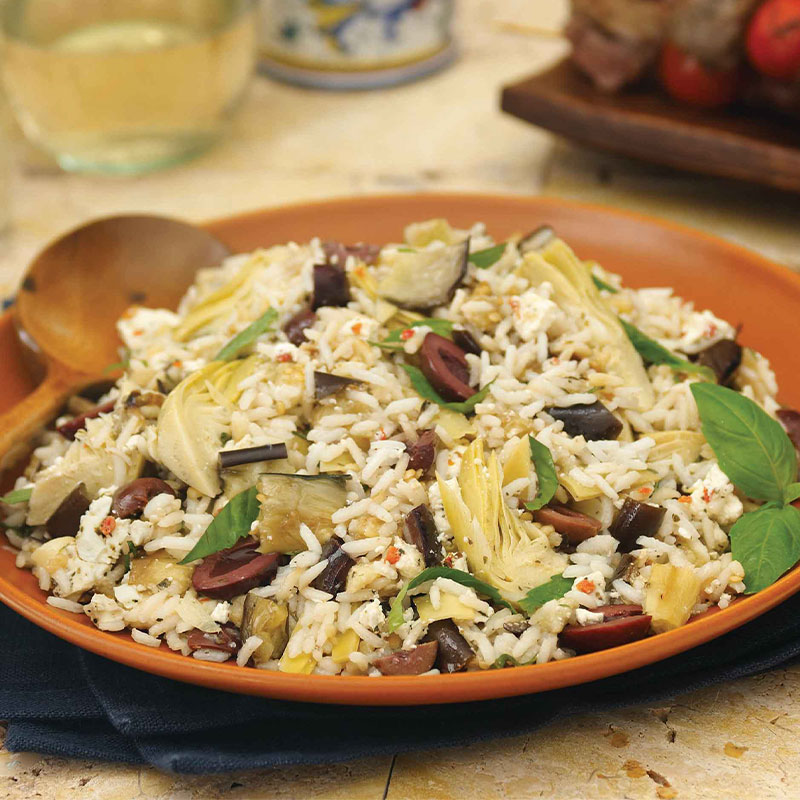 A large serving of Mediterranean Eggplant, Artichoke and Feta Rice Salad on a brown plate.