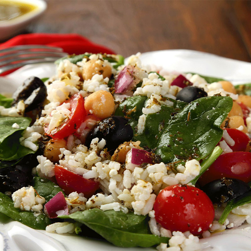 A closeup image of Mediterranean Rice Salad on a white plate with dressing in the distance.