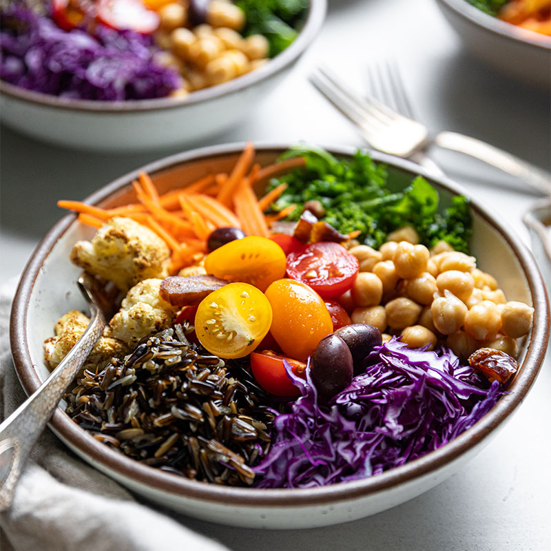 Side view of a Mediterranean Wild Rice Bowl topped with an assortment of colorful vegetables.