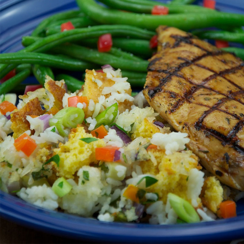 Close up of Mimi's southern rice dressing with grilled chicken and green beans on a blue plate.