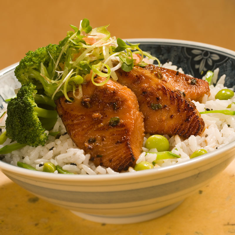 Close up view of miso and soy glazed salmon over rice with broccoli and edamame in a bowl.