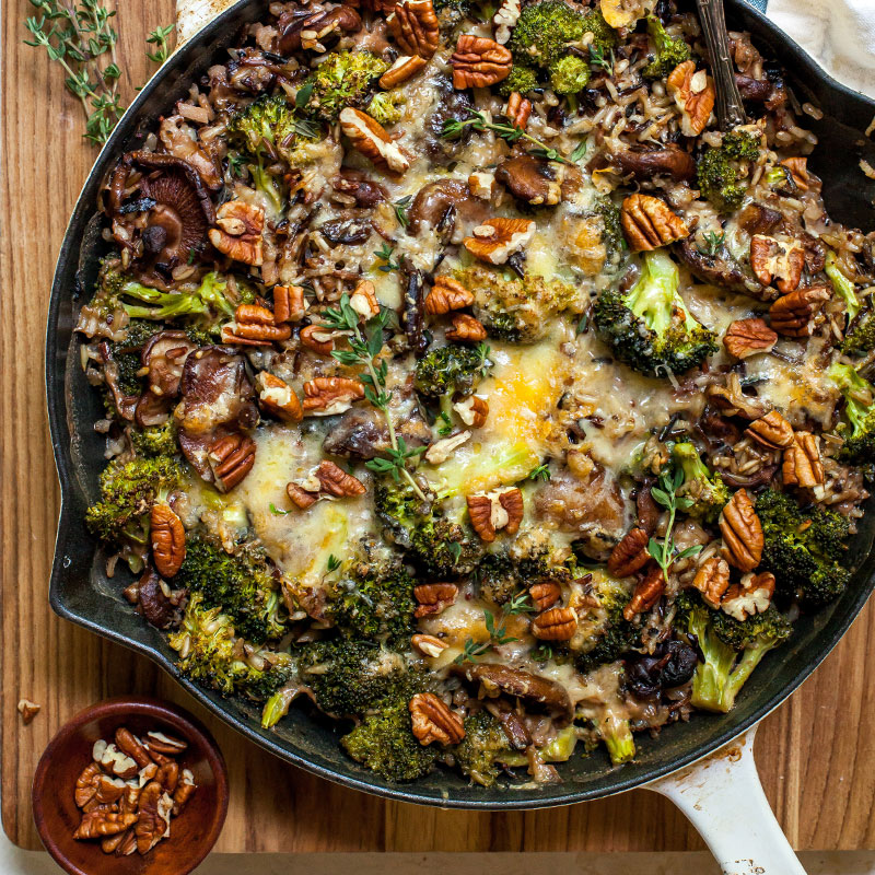 Overhead view of wild rice and cheesy broccoli casserole in a skillet.