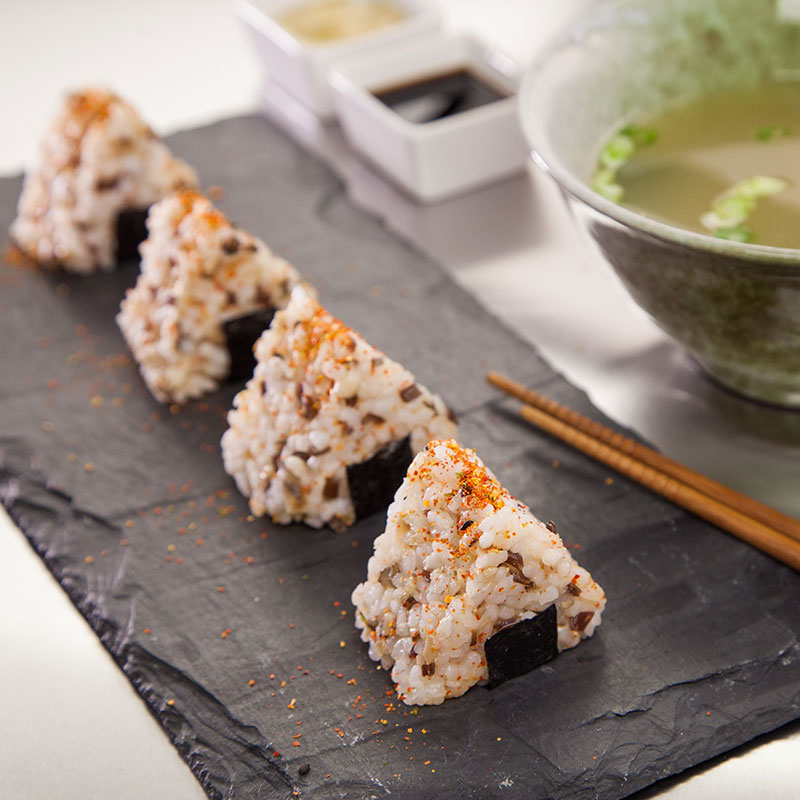 Side view of onigiri on a slate serving platter with miso soup on the side.
