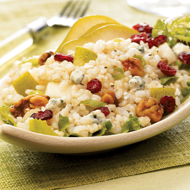 Pear and Walnut Rice Salad on a serving platter with drizzled Blue Cheese Vinaigrette.