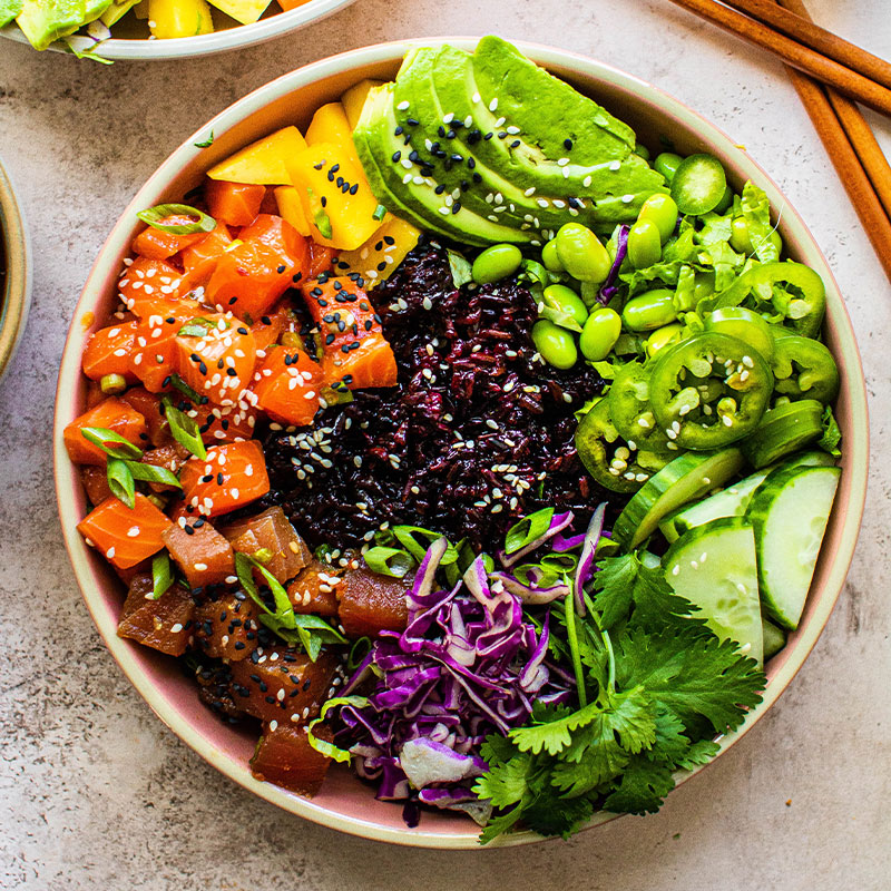 Overhead shot of a colorful poke bowl with purple rice.