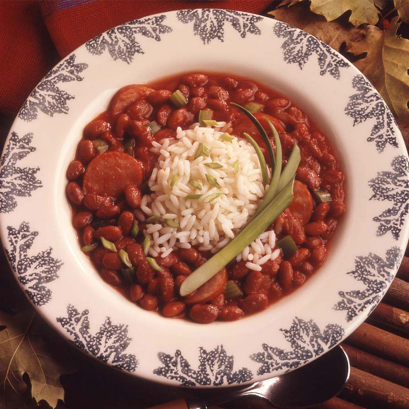 Overhead shot of a cup of white long grain rice on top of and surrounded by red beans and sausage.