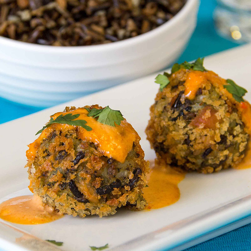 Close up view of Saigon style wild rice and salmon fritters on a white plate garnished with red curry mayonnaise.