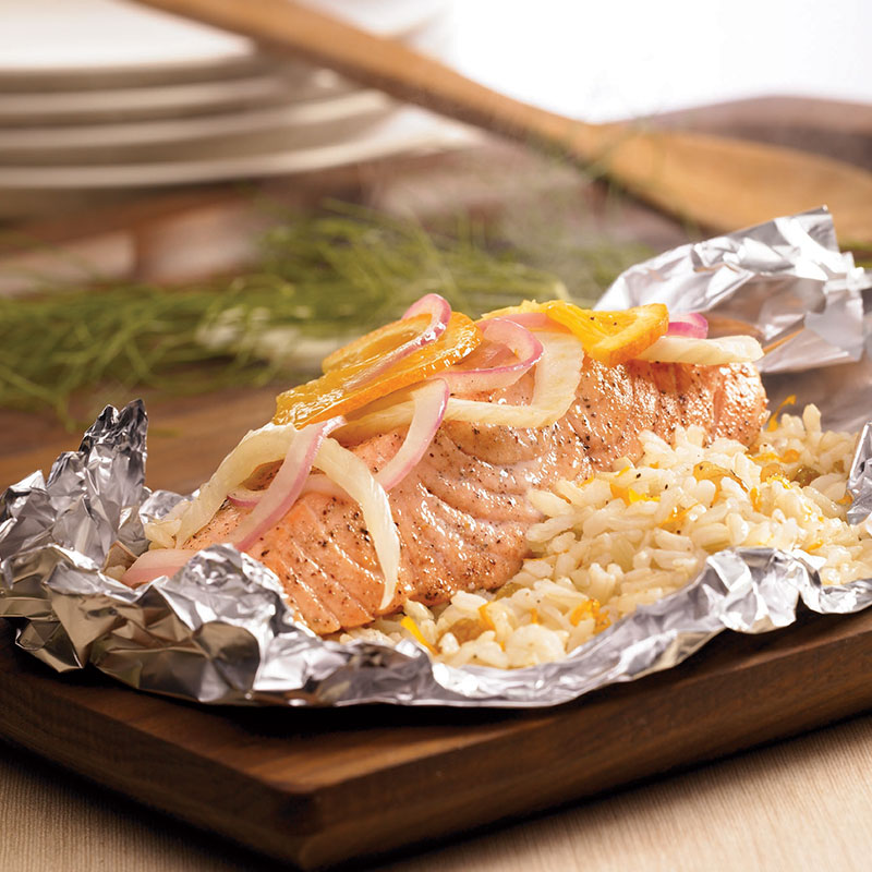 Side view of salmon and rice packets with fennel, orange, and raisins on a wood platter.