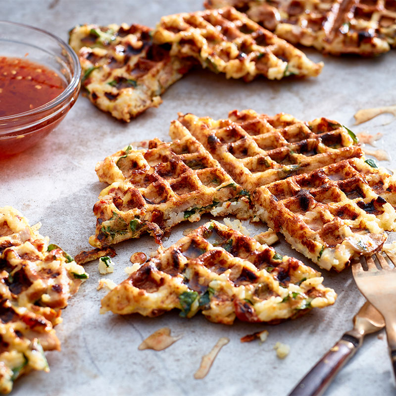 Close up image of a Savory Rice Waffle with additional waffles in the background.