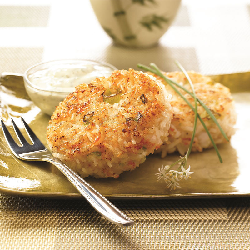 Two Shrimp and Rice Patties on a plate with Creamy Cilantro Sauce in the background.