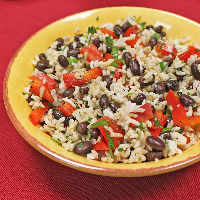 Side view of southwest black bean and brown rice salad in a yellow bowl.