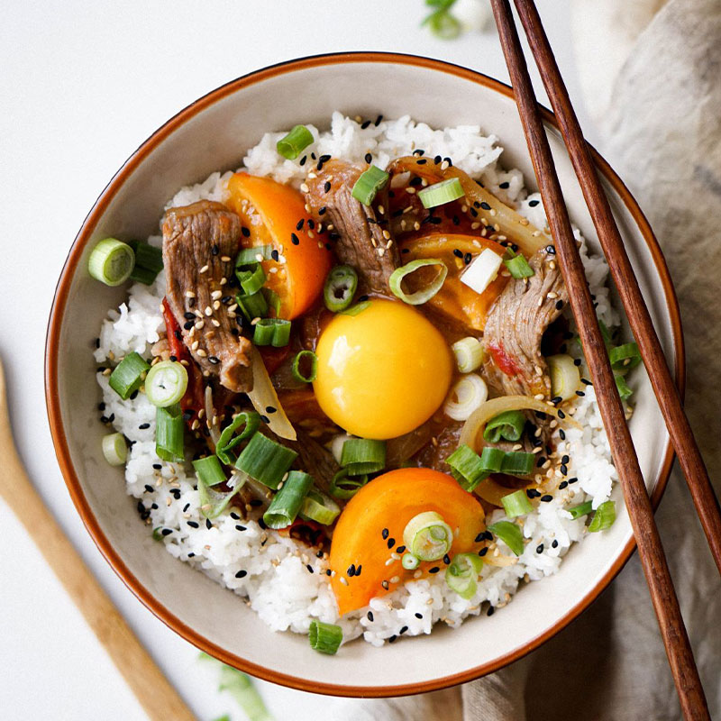 Overhead shot of a bowl with a bed of white rice topped with stir fried orange tomatoes, beef, and an egg yolk.