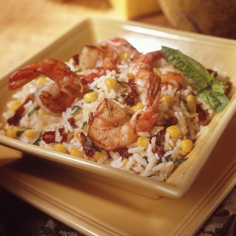 In a square bowl a bed of white rice with corn is topped with shrimp.