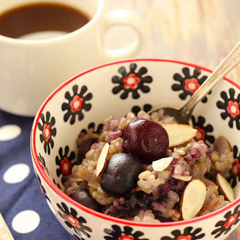 A serving of Sweet Cherry Almond Breakfast Risotto in a coffee cup with a cup of coffee in the distance.