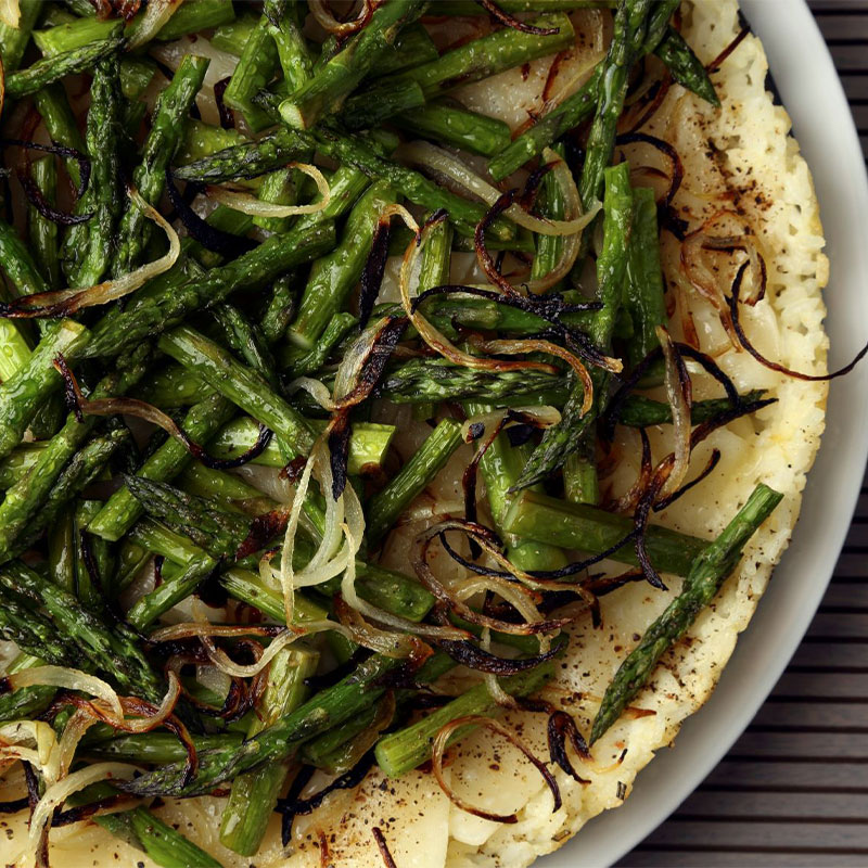 Overhead shot of a complete Swiss & Asparagus Rice Tart topped with asparagus halves and onion.