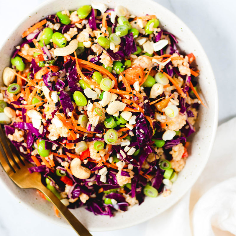 Overhead shot of a rice salad filled with peanuts, edamame, carrots slices, red cabbage, and green onion in a bowl.