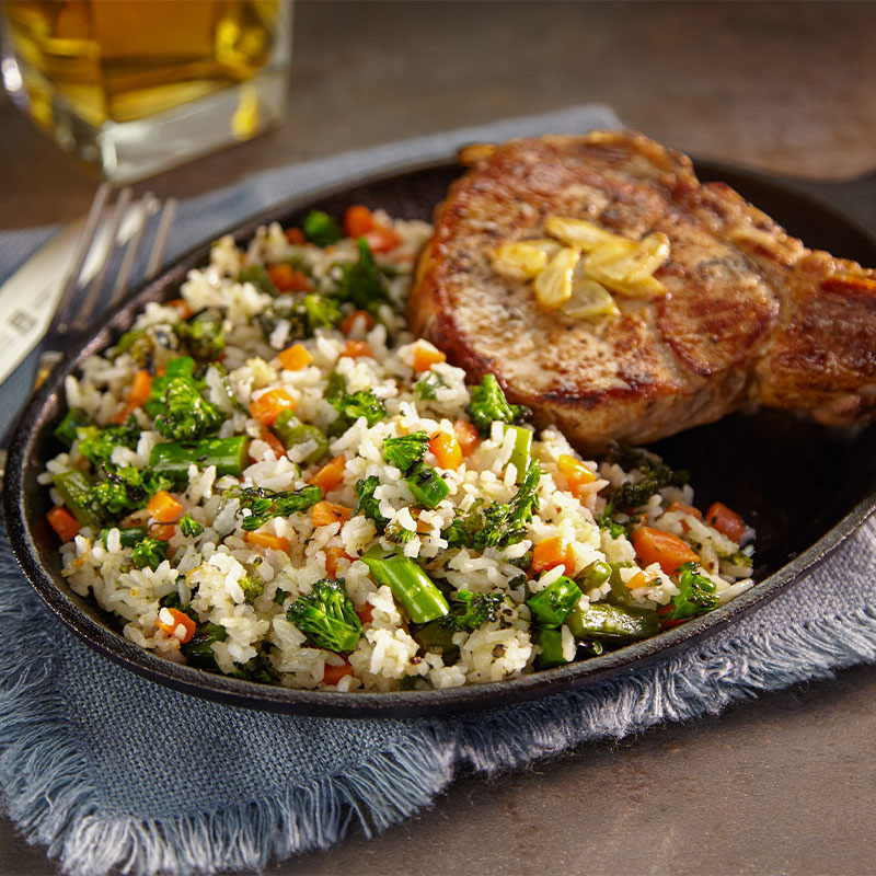 A close up image of toasted garlic rice with broccoli and carrot pieces exposed next to a porch chop on a skillet.