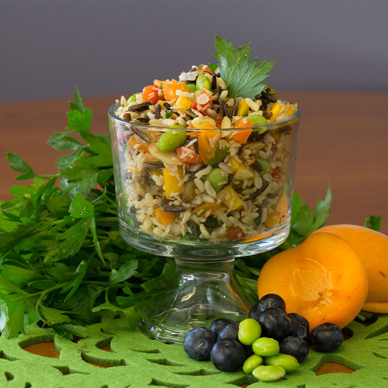 A transparent cup filled with tropical wild rice medley salad.