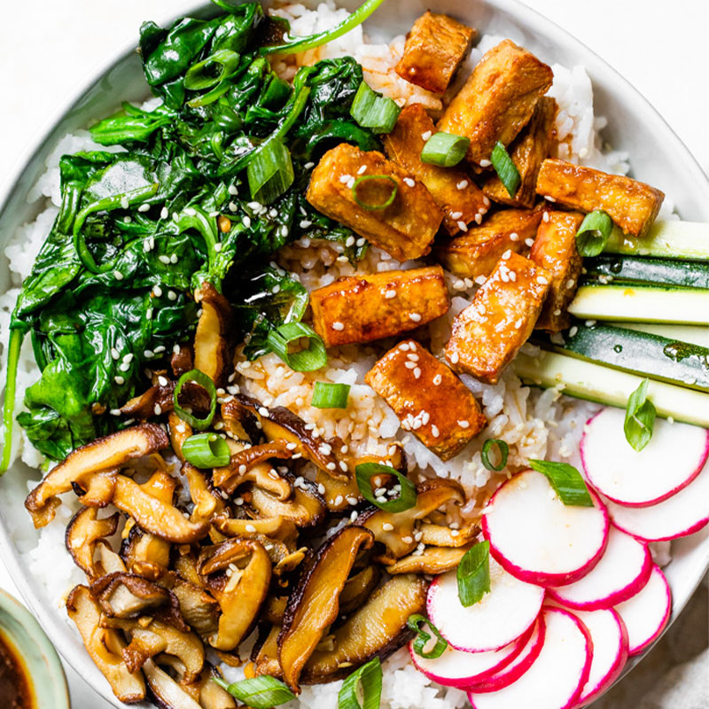 Overhead image of white rice topped with spinach, cooked tofu, mushrooms, and cucumbers in a white bowl.