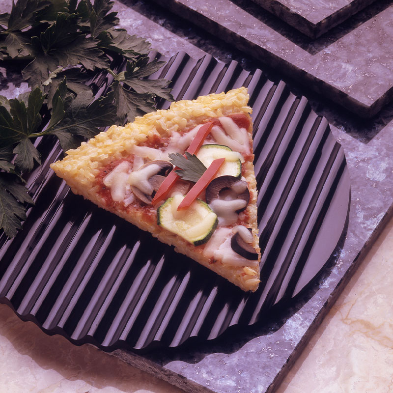 Overhead shot of a single slice of vegetable rice pizza where rice grains can be spotted in the crust.