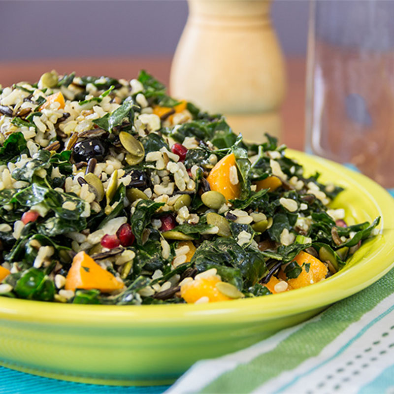 Side view of a yellow dish filled with Wild & Brown Rice, Massaged Kale Salad.