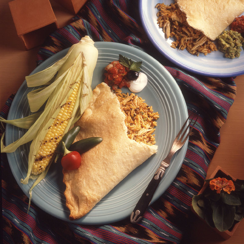One half of a Ya Gotta Empanada with yellow rice falling out on to the plate next to a piece of corn.