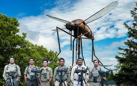 Men standing behind a row of camera tripods, enormous mosquito statue in background