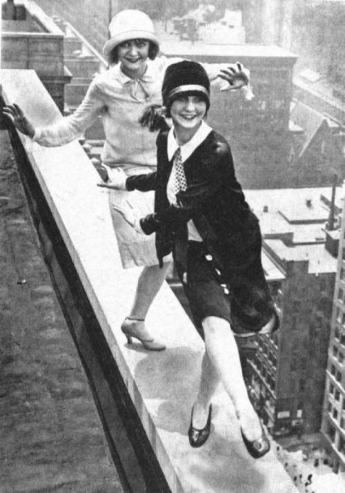 B/W photo of two1920s flappers dancing on a skyscraper ledge