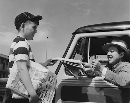 Black & white photo of newsboy selling tabloid newspaper to man in car wearing white fedora