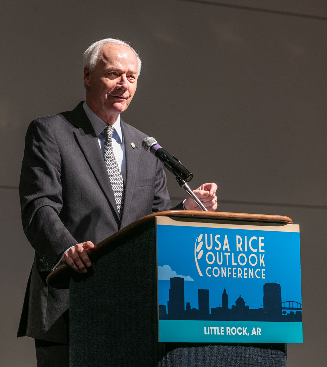 Older white man wearing business suit stands in front of podium with USA Rice Outlook Conference Little Rock AR sign