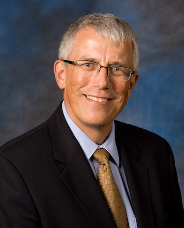 White man with gray hair wearing glasses and a dark business suit and brown tie