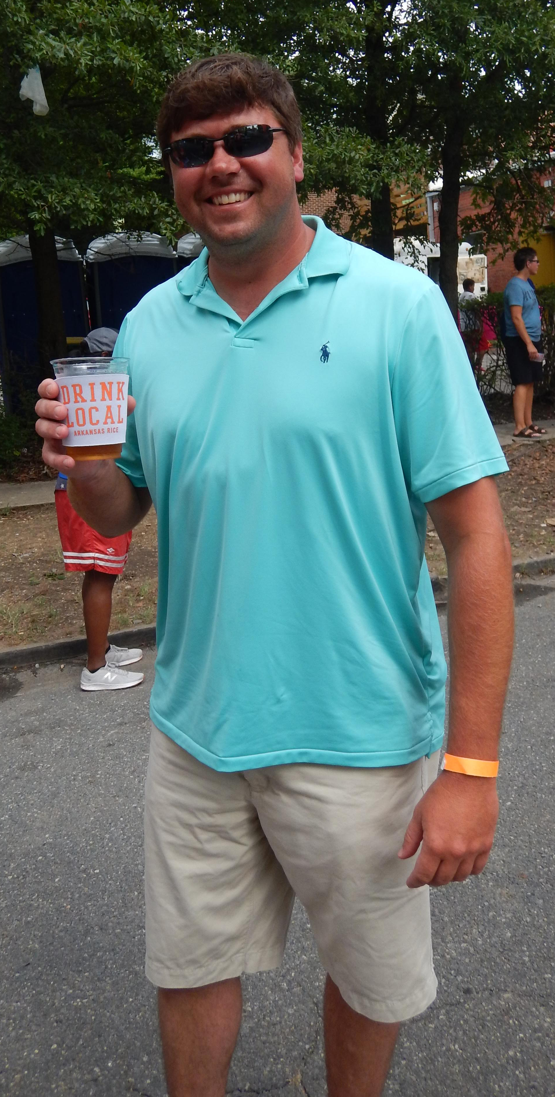 "Eric Vaught at Block the Rock Festival, wearing aqua shirt & tan shorts, holding a glass that says ""Drink Local"""