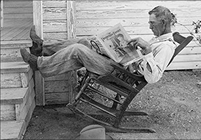 Vintage photo of old man wearing overalls & reading newspaper, rocking back in rocking chair with his feet on steps