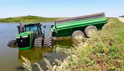 Green tractor and cart stuck in in flooded ditch