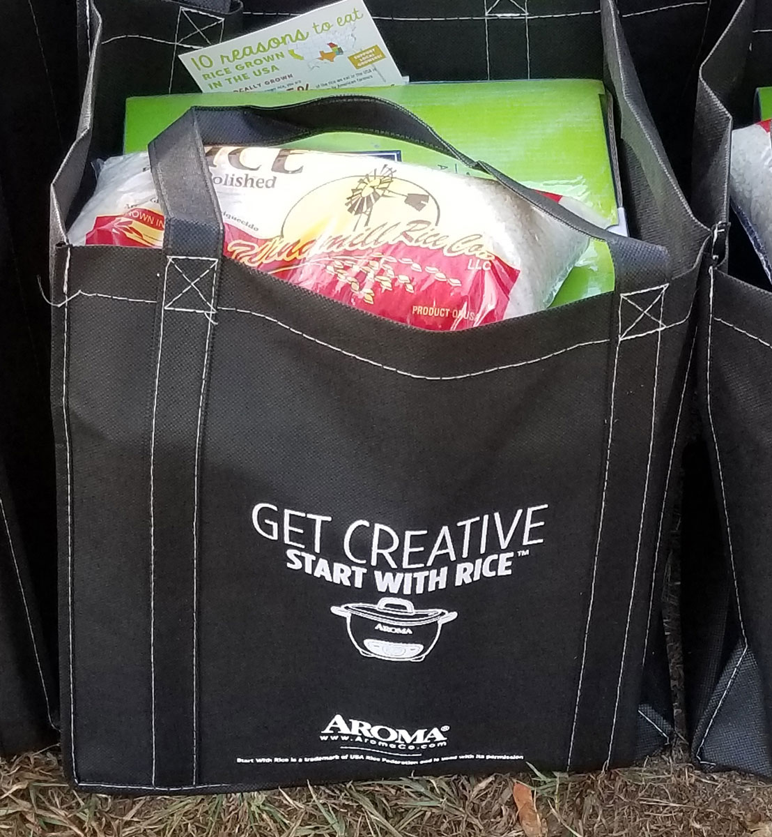 "Black bag with ""Get Creative Start With Rice"" written on side filled with bag of rice and rice cooker in a box"