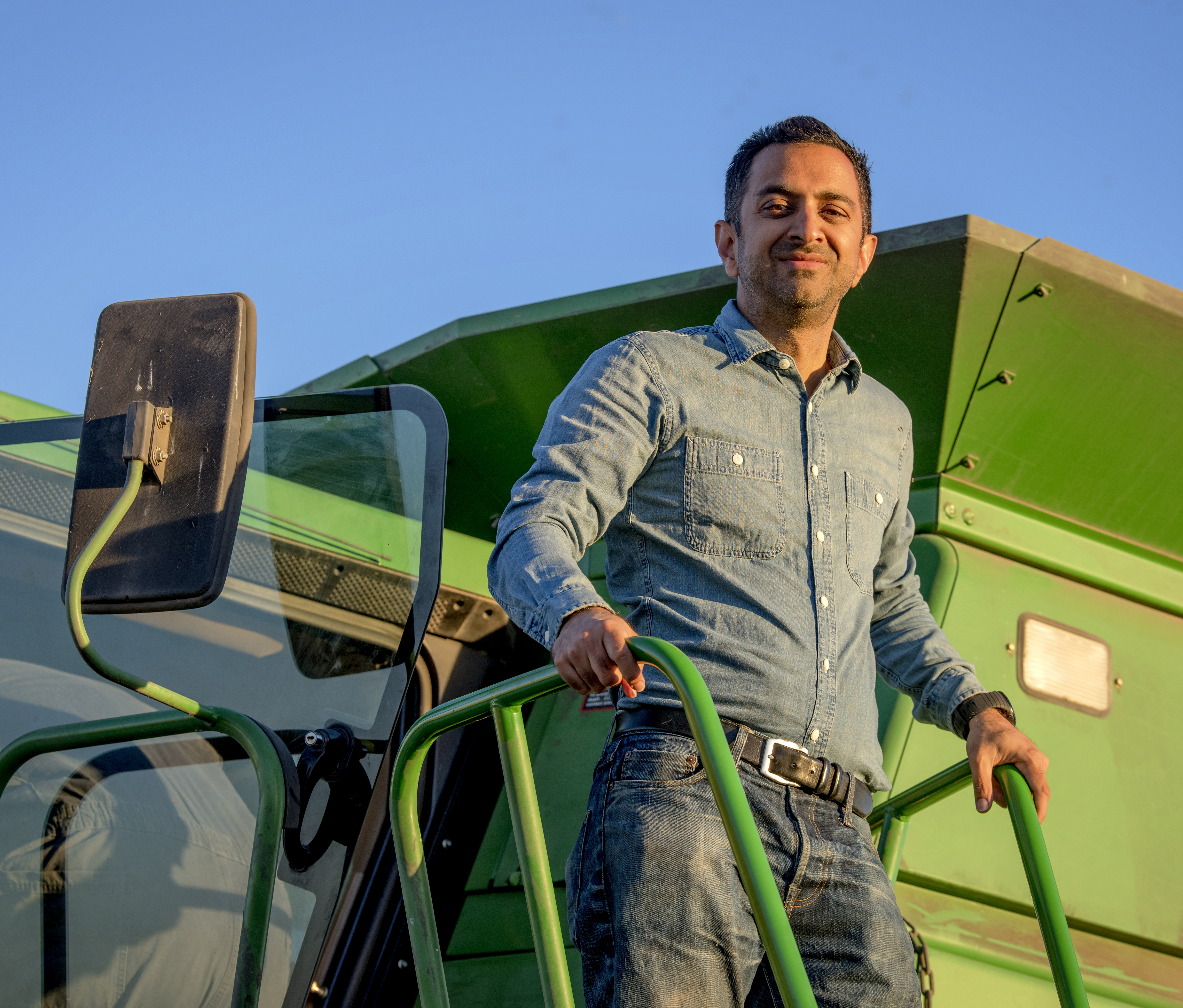 Farmer Imran Khan, wearing denim shirt & blue jeans, stands outside green combine