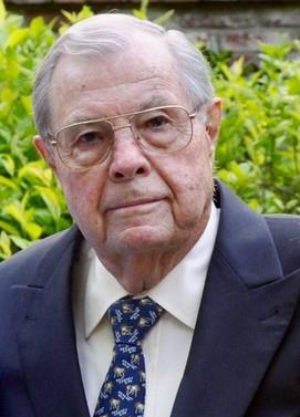 Old white man wearing wire rimmed glasses and suit & tie