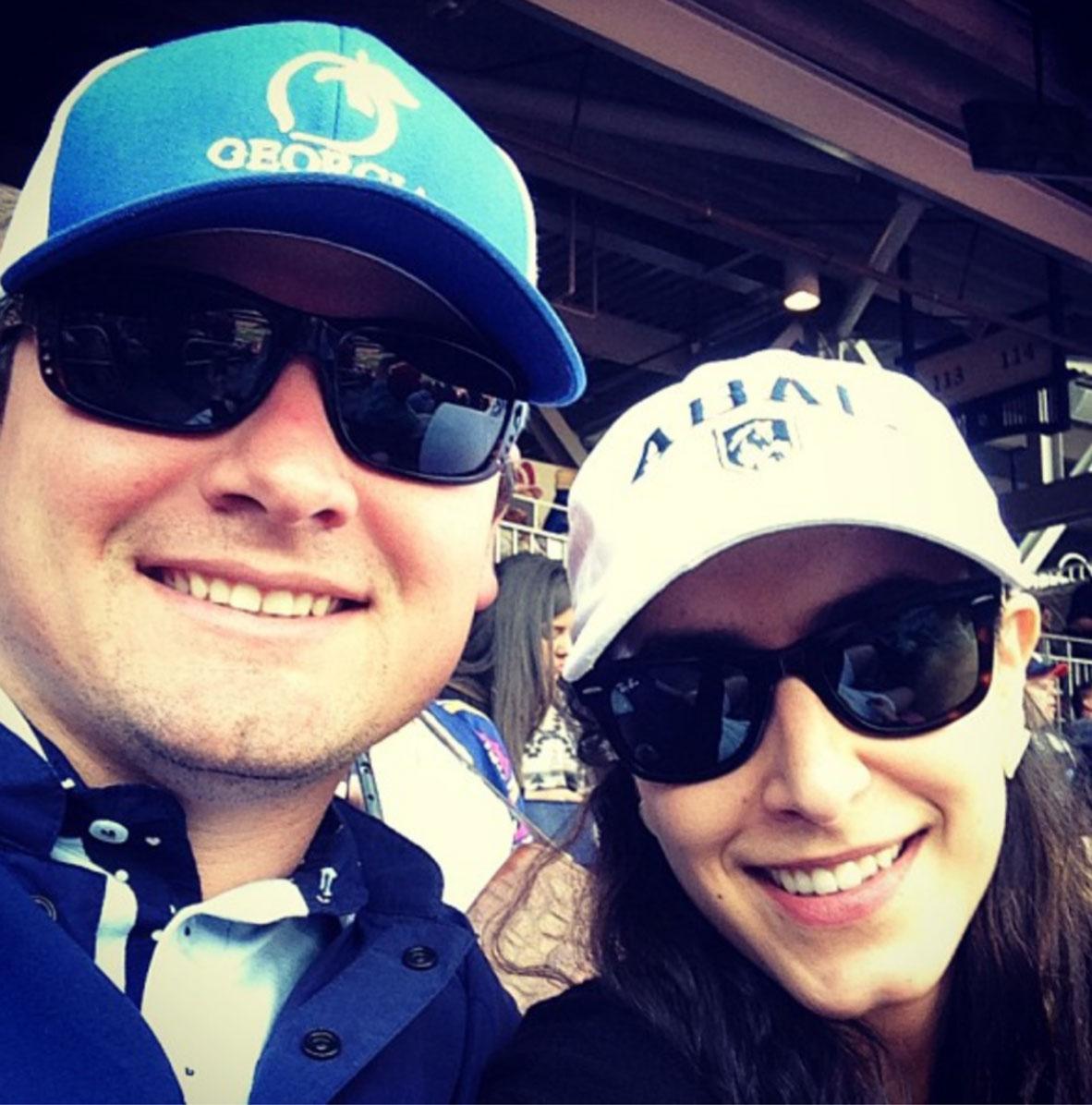 Closeup of man and woman wearing baseball caps and sunglasses