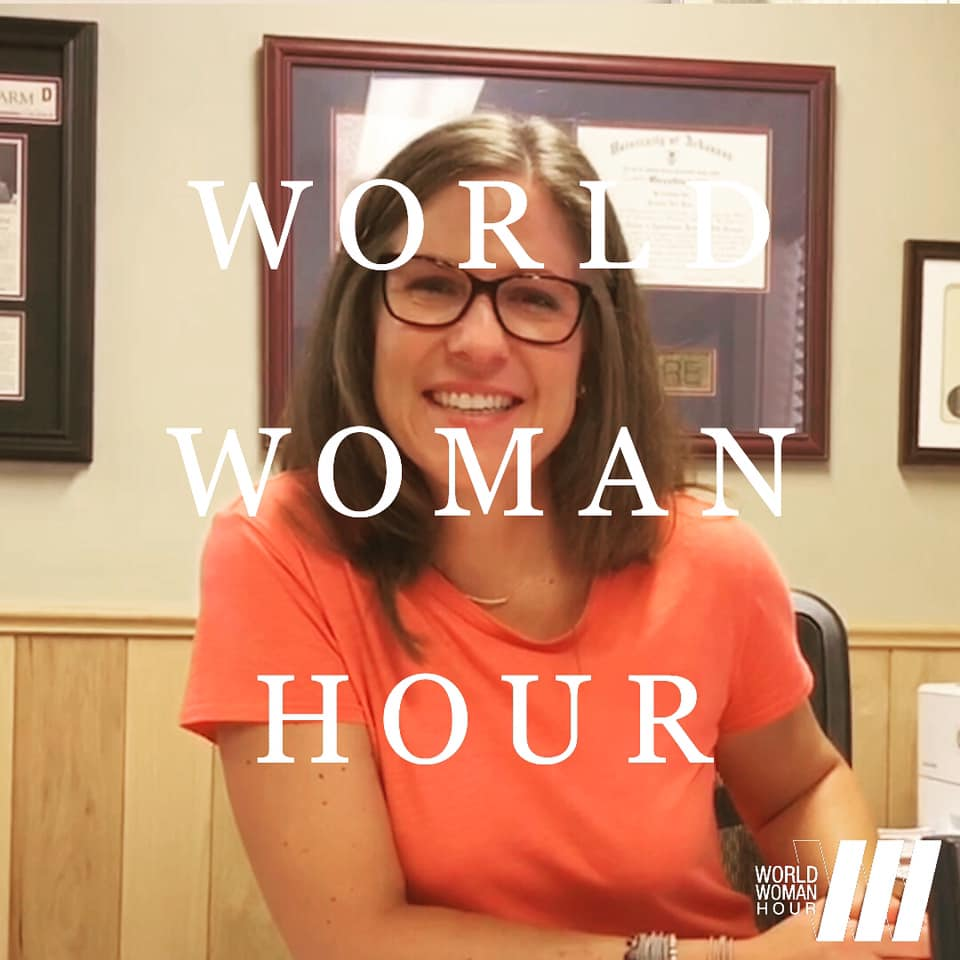 "White woman with brown hair, wearing horn-rimmed glasses, with text ""World Woman Hour"" superimposed over photo"