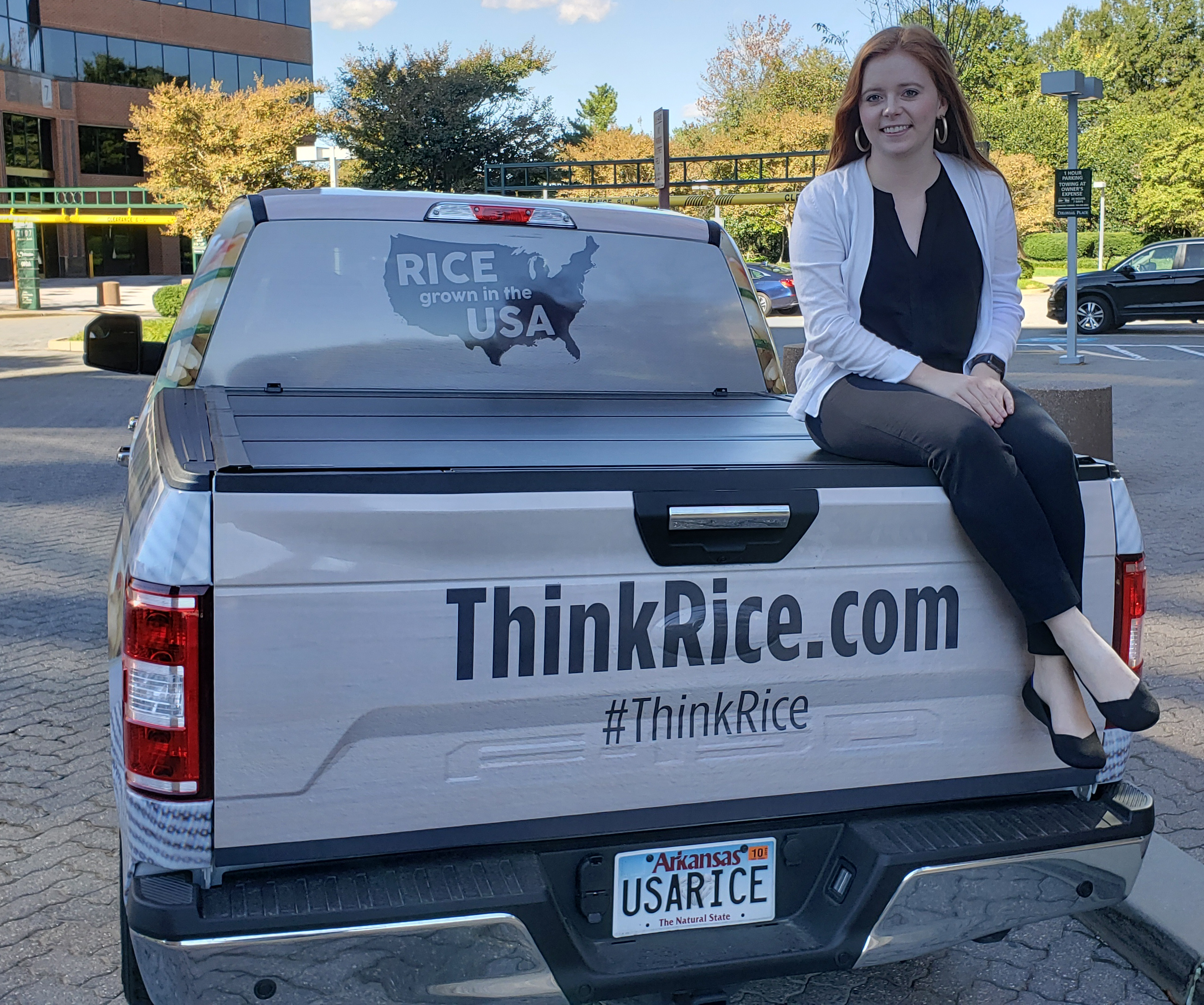 Red-haired woman sits on back of Think Rice pickup truck