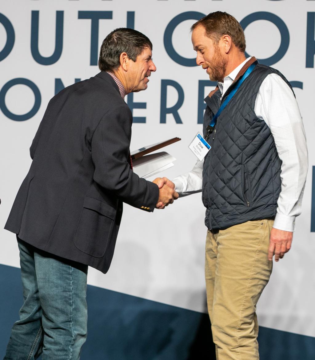 Two men talk and shake hands during award presentation