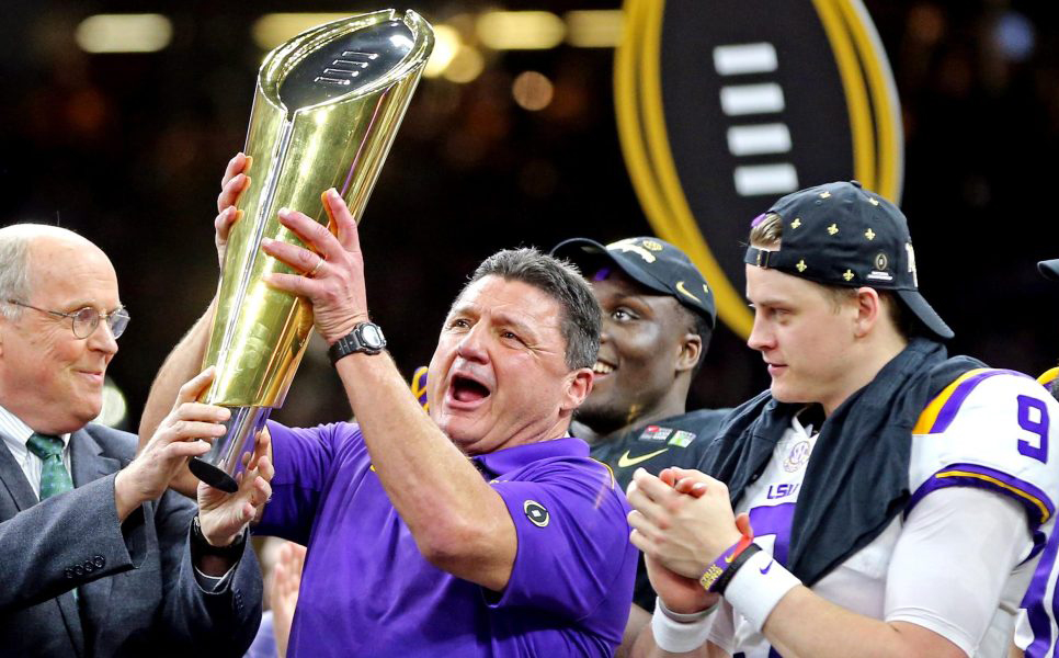 LSU Coach Joe Orgeron holds gold championship trophy while team members look on