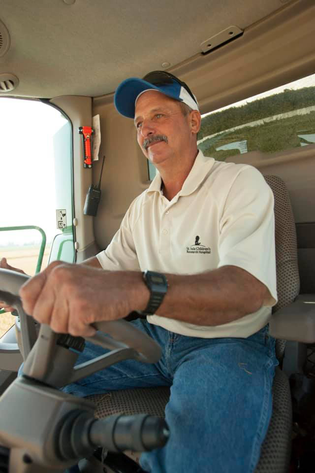 Mark Wimpy, man at the wheel of a combine, wearing white short-sleeved shirt and ball cap
