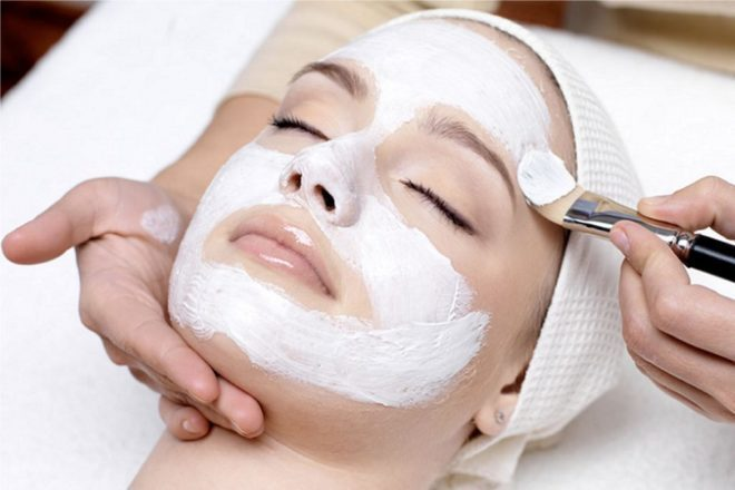 Rice Face Mask Application on female face, makeup brush coating white substance on woman whose eyes are closed