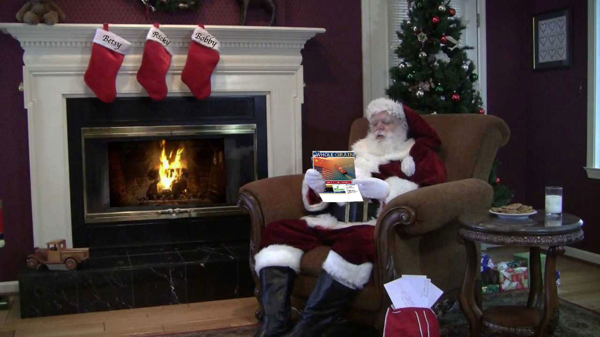 Santa reads newspaper while sitting in chair by fireplace where stockings are hung