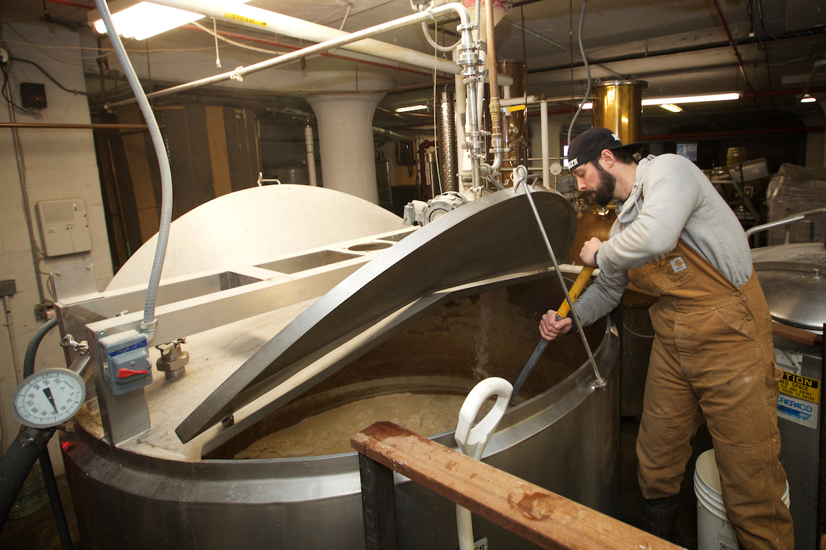 Soju brewer Brandon Hill wearing brown overalls stirs mash in large metal vat, Clay Williams photo-190124
