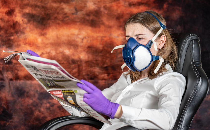 Woman wearing gas mask and purple gloves sits in chair reading a newspaper